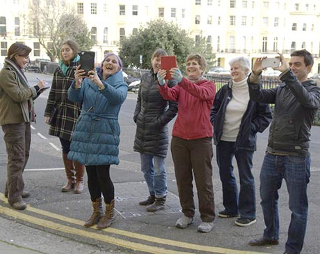 A group of volunteers and researchers testing VisAge software by holding up various mobile devices. In the background can be seen the Regency houses of Brunswicvk Square, Hove.
