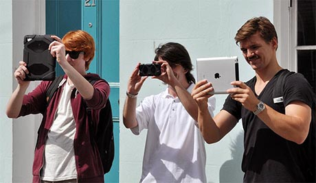 Three people holding mobile devices at eye level to look at images